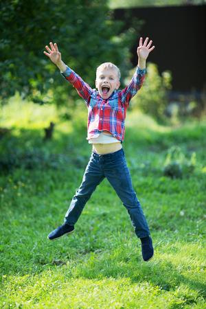 little boy joyfully jumping in the summer in the garden 写真素材