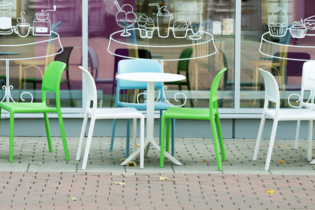 white and green plastic tables and chairs of a street cafe 写真素材