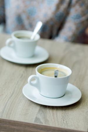 cup of coffee on a table in a cafe close-up with shallow depth of field