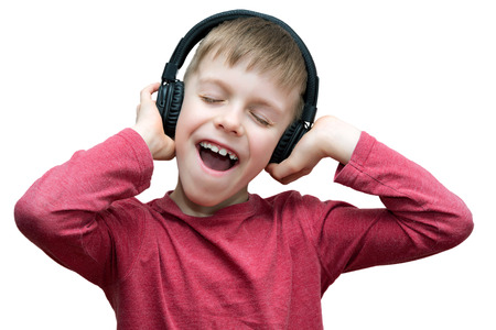 seven year old boy with headphones singing on white background