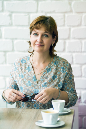 middle-aged woman with a cup of coffee at a table in a cafe