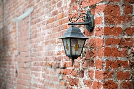 vintage lantern on a red brick wall close up