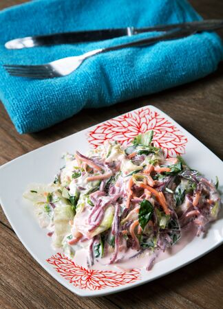 vegetable salad with mayonnaise dressing and cutlery on a rustic table 写真素材