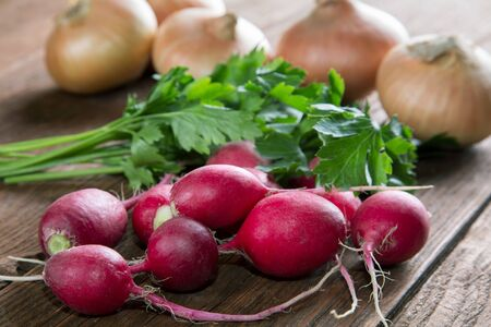 radish onion and parsley vegetables on a rustic table