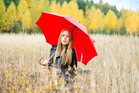 girl with a red umbrella among the grass in autumn