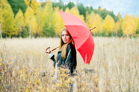 girl with a red umbrella in the field on an autumn afternoon on a background of forest with yellow leaves