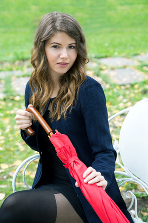 girl with a red umbrella in her hands on a park bench