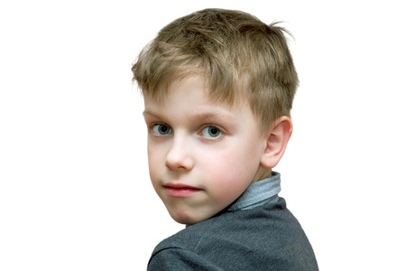 the boy looks half-turned right into the camera on a white background