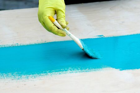brush with turquoise paint close-up on a painted surface background 写真素材
