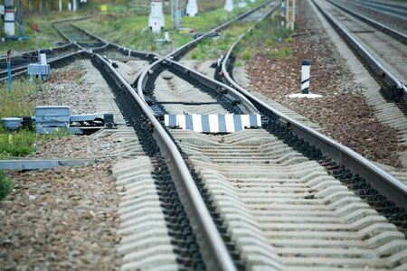 railway rails with an arrow at the station