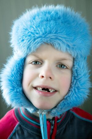 seven-year-old boy without front teeth in a winter hat