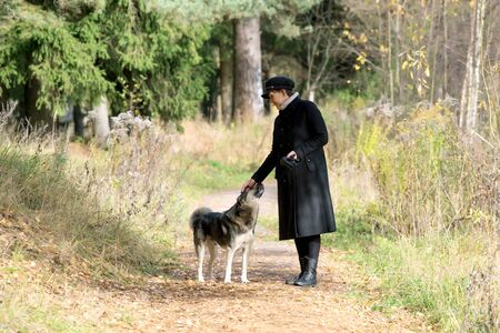 middle-aged woman stroking a dog for a walk in the park