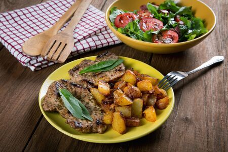 plate with fried potatoes and vegetable salad on a rustic table
