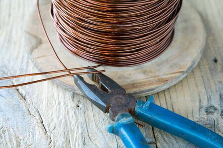 coil of copper wire and pliers close-up