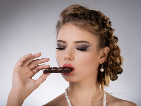 Portrait of young  brunette girl eat chocolate photo