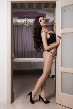 Photo of young  girl in erotic lingerie posing in the interior photo