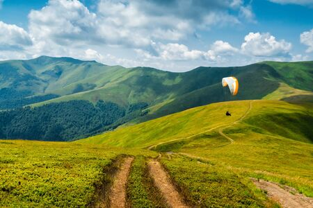 paraglider: Landscape with clouds in the mountains, paraglider,parachute,glider Stock Photo