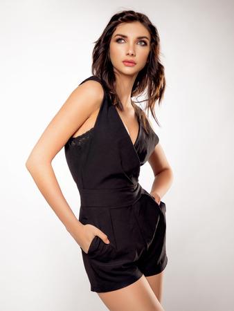 overbearing: Brunette girl posing in black dress Stock Photo