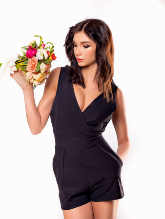 Brunette girl posing in a black dress with a bouquet of flowers