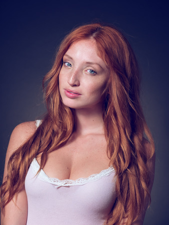 Red-haired, beautiful girl emotionally posing in underwear