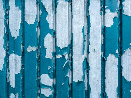 The texture of the galvanized fence with peeling paint.