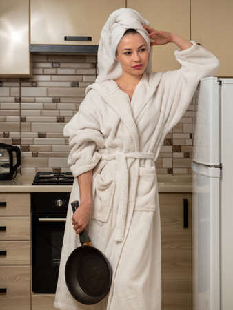 Young woman, housewife in the kitchen in a white, bathrobe with a frying pan.