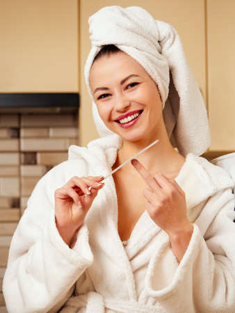 A young woman, a housewife in the kitchen, makes a manicure after a shower in a white bathrobe. Reklamní fotografie
