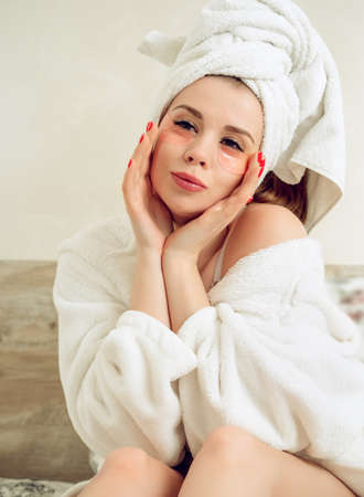 Young, beautiful woman cares for the skin of the face. Woman in robe after shower Reklamní fotografie