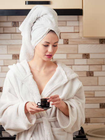 After a shower, a young, beautiful woman housewife in a white robe and a towel on her head is thinking with a cup of coffee in the kitchen. Reklamní fotografie