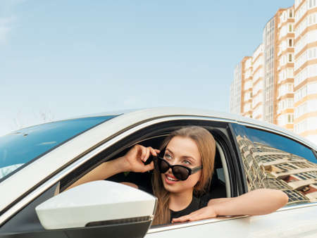 Modern beautiful woman businesswoman with glasses peeks out of her car.