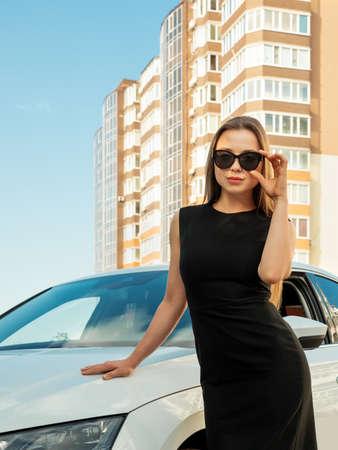 Modern beautiful woman businesswoman stands near her car. Stockfoto