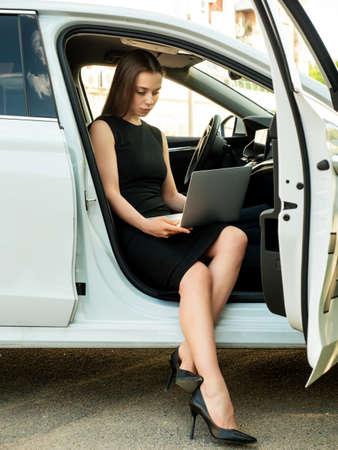 Modern woman businesswoman working on laptop in her car. Stockfoto