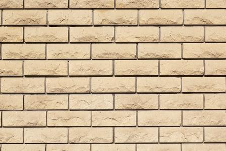 textured wall: Wall of beige textured bricks