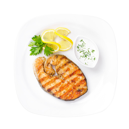 Grilled salmon steak with sauce and lemon