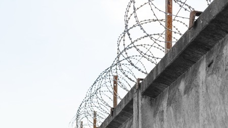 Concrete fence with a barbed wire