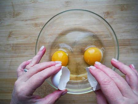 Female hands break an egg, cooking egg dishes Stockfoto