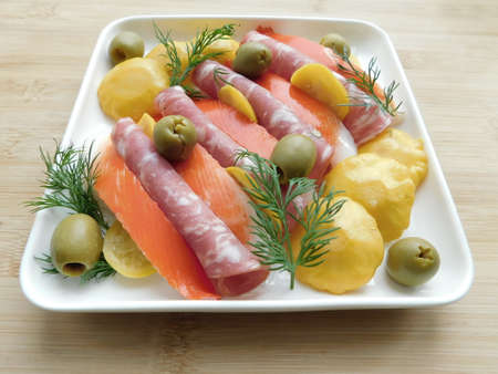 salami, olives and squash on a plate on a wooden table. traditional snacks Standard-Bild