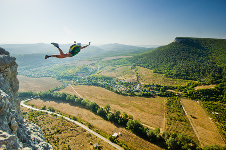 Base-jumper salta dalla scogliera al sorgere del sole in montagna Archivio Fotografico - 34781256