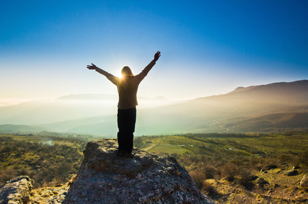 自由の女の子は太陽に対して山の中を手で 写真素材