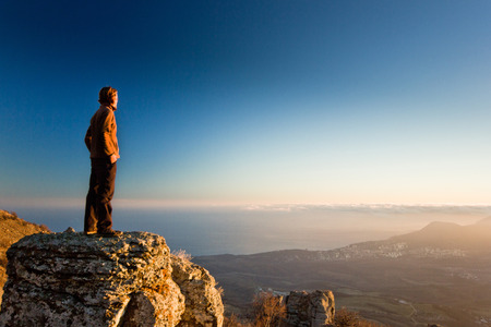 青空と夕日で山の絶壁の思考の男