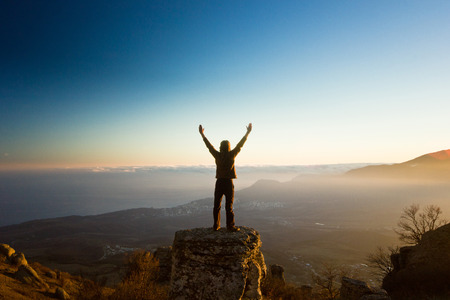 man arm: freedom man with hands up in the mountains against sun Stock Photo