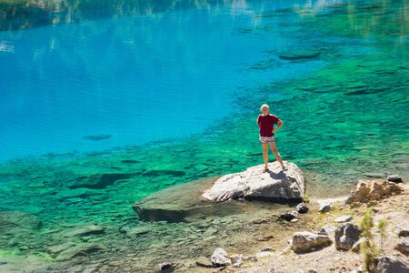 t short: girl in red t-short near deep blue lake standing and smiling on a stone Stock Photo