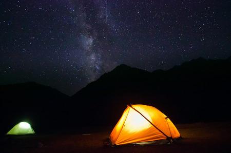 ランプで強調表示されたテントが付いている山の上の天の川