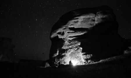 cave dweller: bounfire lights big rock with sitting man and stars on the sky Stock Photo