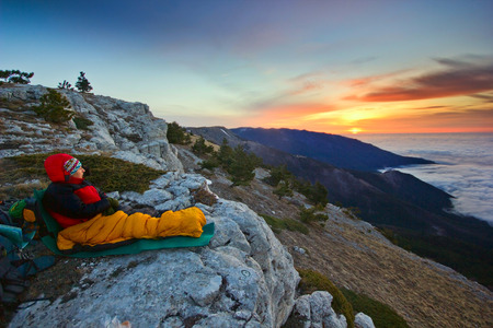 girl sitting in yellow sleeping bag on a cliff in mountains at sunrise