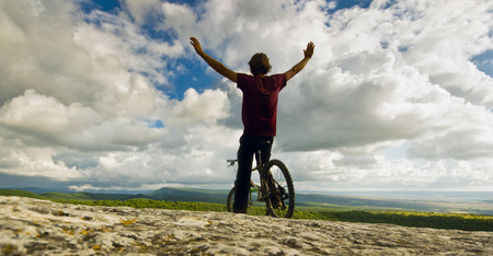 t short: man with hands up on bicycle with covered by forest hills and clouds on sun