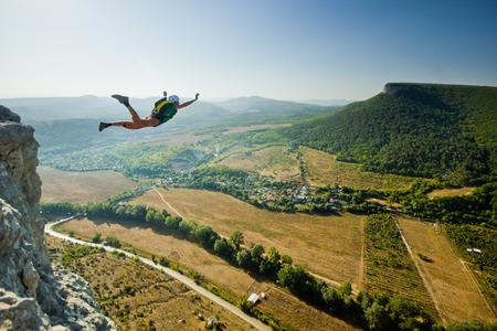 Base-Jumper springt von der Klippe bei Sonnenaufgang in den Bergen