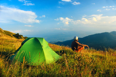 awaking: man sitting near tent in the mountains with clouds on the sky