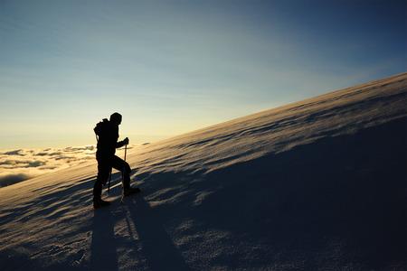 女の子は太陽に対して雪の斜面を登山します。