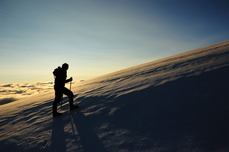 girl climbs mountain with snowy slopes against sun Stock Photo